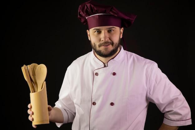 Il ritratto dell'uomo positivo del cuoco unico in uniforme tiene gli utensili da cucina in legno