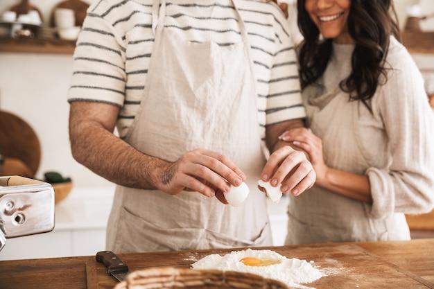 Ritratto di coppia positiva uomo e donna 30s che indossano grembiuli che cucinano pasticceria con farina e uova in cucina a casa