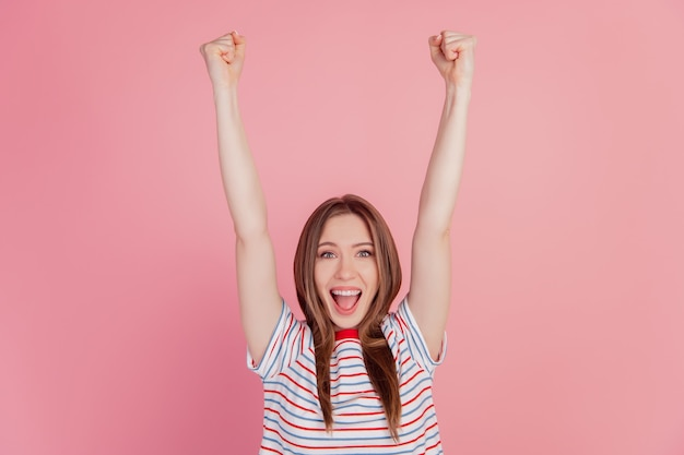 Il ritratto della signora pazza positiva alza le mani celebra la vittoria a bocca aperta su sfondo rosa