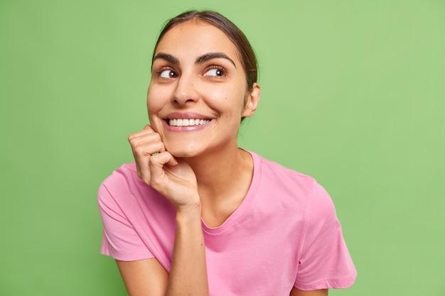 Il ritratto di una giovane donna bruna carina positiva tiene la mano sotto il mento sorride ampiamente immagina qualcosa di buono o piacevole indossa una maglietta rosa isolata sul muro verde