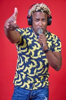 Ritratto di un bellissimo uomo africano che si gode positivamente con un microfono e delle cuffie in testa