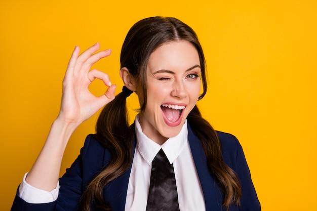 Il ritratto dell'adolescente eccitato positivo del liceo mostra il segno ok l'occhiolino