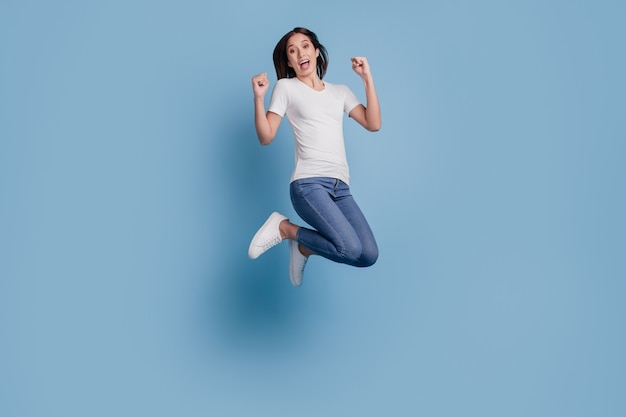 Il ritratto della signora pazza divertente positiva salta celebra la vittoria su fondo blu
