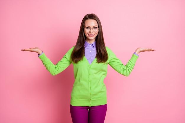 Il ritratto della ragazza positiva tiene il copyspace della mano isolato sopra il fondo rosa di colore