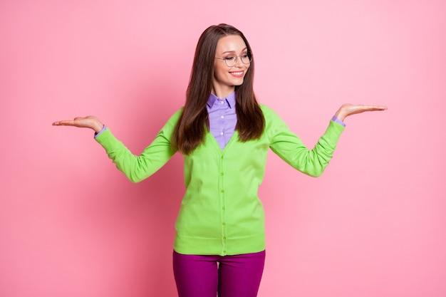 Ritratto di ragazza positiva tenere la mano guardare copyspace indossare pantaloni isolati sfondo di colore rosa