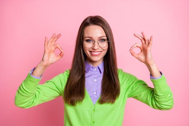 Il ritratto della ragazza positiva mostra il segno giusto isolato sopra il fondo di colore pastello