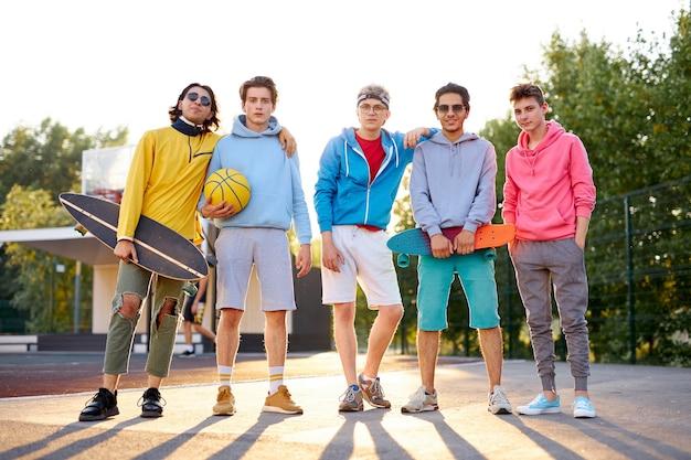 Ritratto di gruppo positivo di giovani è venuto a giocare a basket