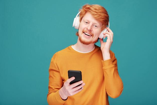Ritratto di uomo positivo bello giovane rossa con la barba che regola le cuffie senza fili mentre si sceglie la traccia musicale sullo smartphone