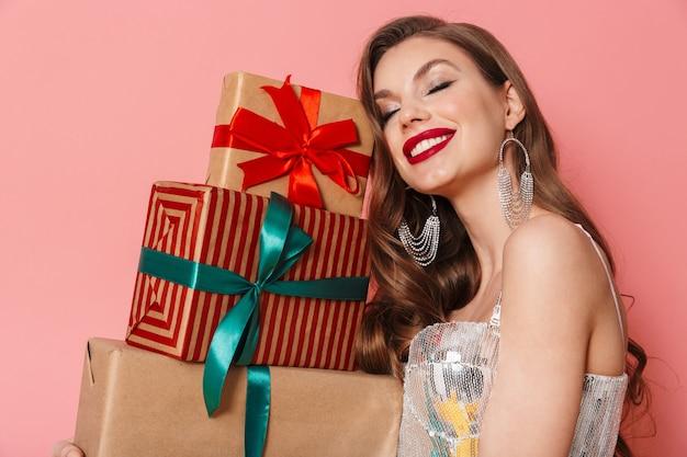 Ritratto di una giovane donna positiva e felice in abito di paillettes luminose isolato su un muro rosa che tiene scatole regalo presenti.