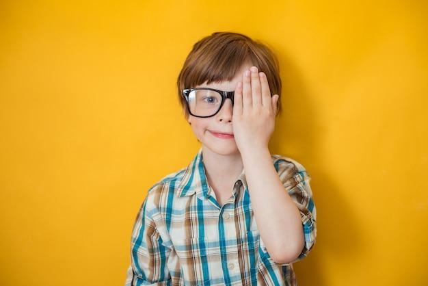Ritratto del ragazzino positivo in vetri. kid a prova di vista dell'occhio. visione, misurazione della vista per i bambini in età scolare. concetto di salute, infanzia e oftalmologia