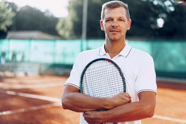 Ritratto del giocatore di tennis maschio positivo con la racchetta che sta al campo in terra battuta vicino alla rete