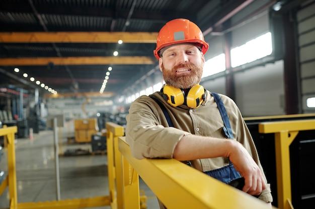 Ritratto di lavoratore maschio positivo in casco arancione che si appoggia su ringhiere metalliche nel moderno negozio di fabbrica