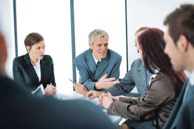Ritratto di un manager positivo con la sua squadra seduto al tavolo