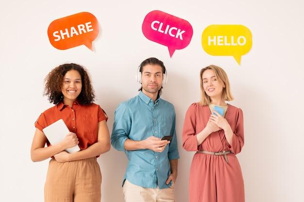 Ritratto di persone multietniche moderne positive che interagiscono sui social media, tag luminosi con attività di social networking sopra di loro