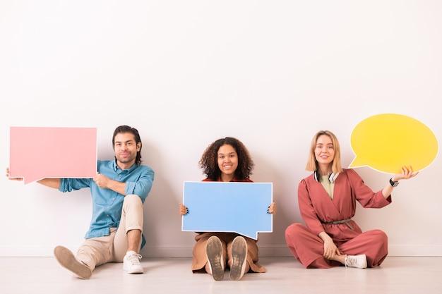 Ritratto di persone multietniche positive che si siedono sul pavimento e che mostrano i tag di dialogo colorati alla macchina fotografica