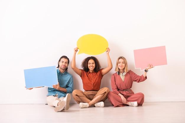 Ritratto di persone multietniche positive che si siedono con i tag del fumetto, restano socialmente connessi con la comunicazione internet