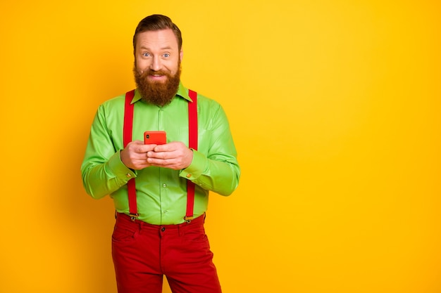 Ritratto di gentiluomo irlandese di redhair capelli rossi positivo utilizzare il telefono cellulare leggere ricerca social media notizie godere di condividere blogging indossare pantaloni di bell'aspetto isolato brillare colore