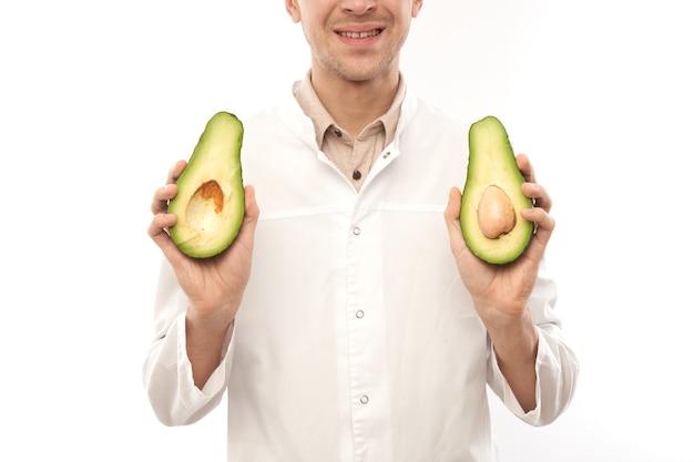 Ritratto di medico nutrizionista maschio sorridente positivo con avocado. pelle sana e bella, cibo dietetico, concetto di perdita di peso