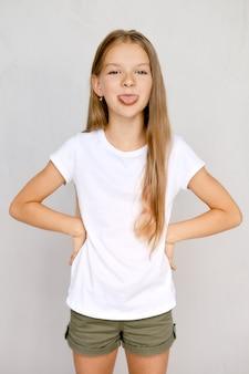Ritratto di ragazza adolescente positiva che attacca fuori lingua