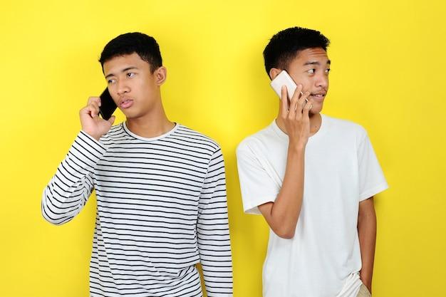 Ritratto di due uomini asiatici positivi comunicano utilizzando lo sfondo giallo isolato dello smartphone
