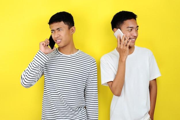 Ritratto di due uomini asiatici sorridenti positivi che comunicano utilizzando lo sfondo giallo isolato dello smartphone