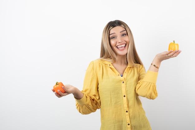 Ritratto della donna positiva che tiene i peperoni dolci variopinti sopra la parete bianca.