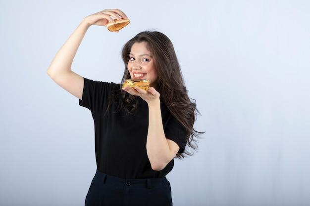 Ritratto di donna positiva in posa con delizioso hamburger sul muro bianco.