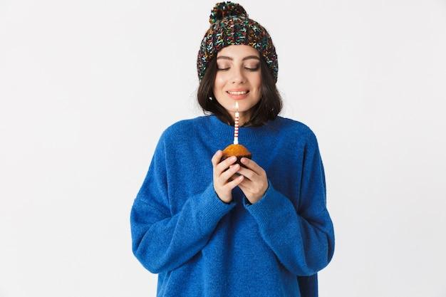 Ritratto di donna positiva che indossa il cappello invernale tenendo la torta di compleanno con una candela in piedi, isolato su bianco