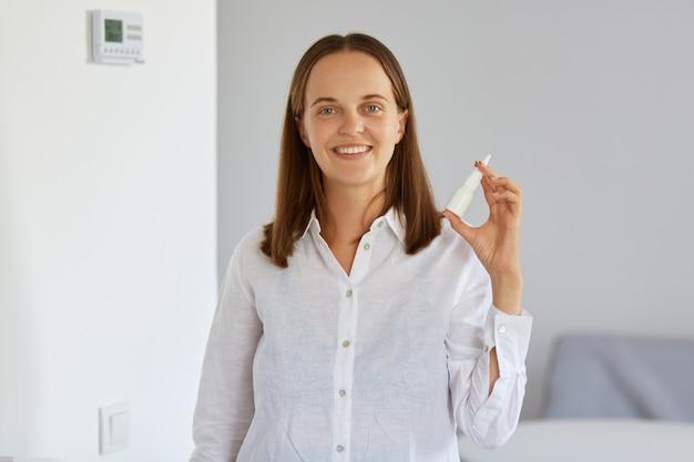 Ritratto di donna positiva con spray nasale in mano, mostrando la medicina che l'aiuta con il naso che cola, guardando sorridendo alla telecamera, assistenza sanitaria.