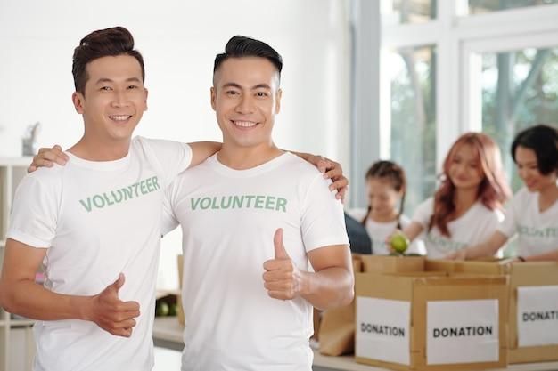 Ritratto di giovani volontari di fondazione di beneficenza positivi che mostrano il pollice in su