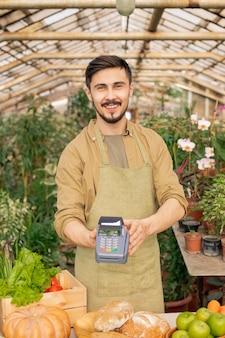 Ritratto di giovane agricoltore positivo con la barba che tiene il terminale di pagamento sopra il bancone alimentare nel negozio di alimentari