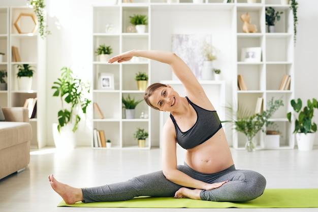 Ritratto di giovane donna incinta positiva in reggiseno sportivo che allunga il corpo con esercizio di yoga a casa mentre si prepara per il parto