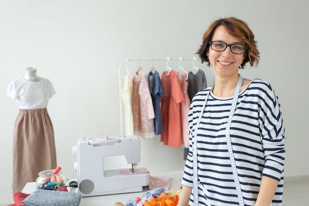 Ritratto di una sarta di giovane donna positiva in piedi sul suo desktop con molti vestiti su una gruccia