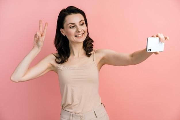 Ritratto di giovane donna positiva in maglietta sorridente e scattare foto selfie sul cellulare