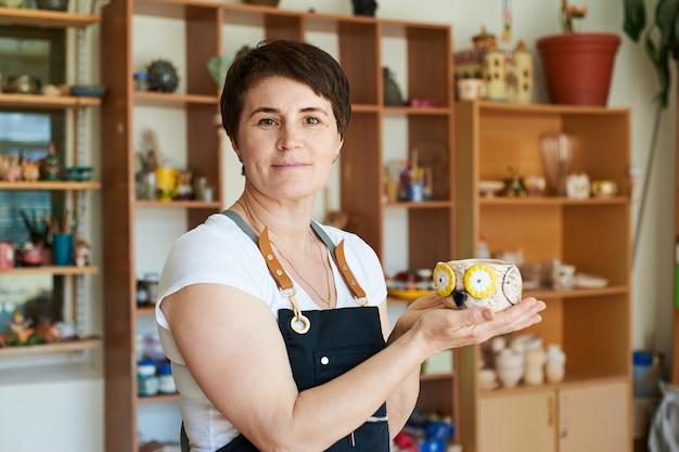 Ritratto di una donna maestra di ceramica che mostra il lavoro finito.