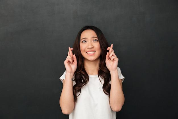 Ritratto di pregare giovane donna che indossa abbigliamento casual accattonaggio dio per favore, guardando in alto con le dita incrociate, isolato su muro grigio scuro