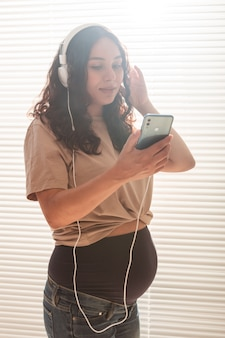 Ritratto di donna incinta vicino alla finestra a casa e ascolto di musica in cuffia. gravidanza e concetto di tempo libero.