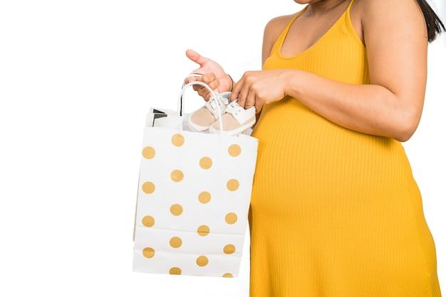 Ritratto di donna incinta che apre un regalo per il neonato su sfondo bianco. maternità e concetto di gravidanza.