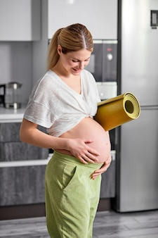 Ritratto di donna incinta in maglietta bianca e pantaloni verdi in piedi abbracciando la pancia