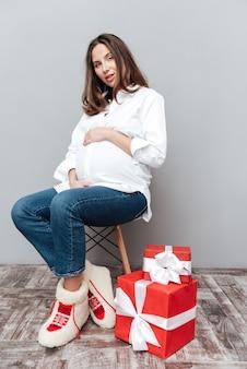 Ritratto di donna incinta con doni a figura intera seduto su una sedia in studio
