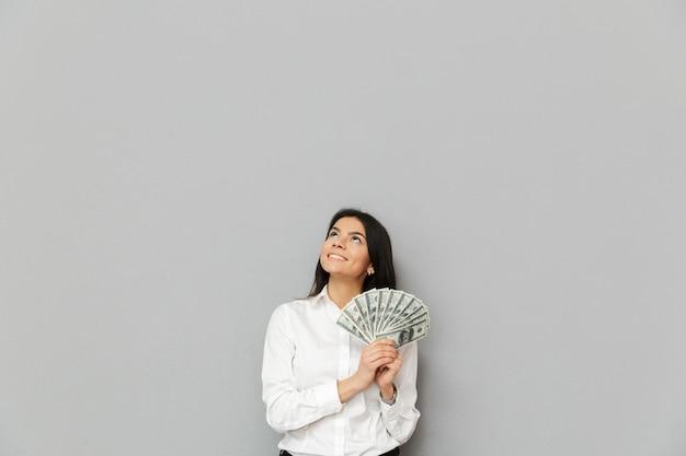 Ritratto di donna adulta abbastanza anni '30 che indossa abiti da ufficio in possesso di denaro contante e guardando verso l'alto su copyspace, isolato sopra il muro grigio