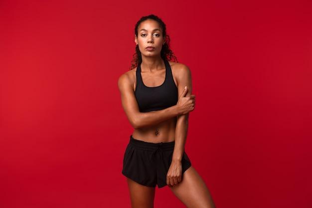 Ritratto di una sportiva abbastanza afroamericana in abiti sportivi neri in piedi, isolato sopra la parete rossa