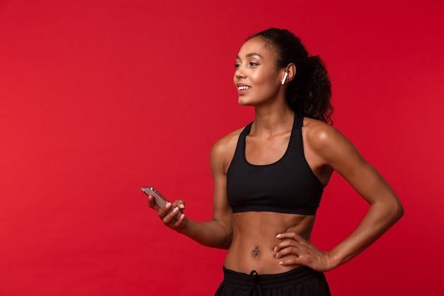 Ritratto di donna abbastanza afroamericana in abiti sportivi neri utilizzando smartphone e auricolari wireless, isolati sopra la parete rossa