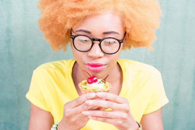 Ritratto di una bella donna africana in maglietta gialla che tiene un dolce dessert con ciliegia sullo sfondo verde