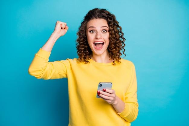 Ritratto di una ragazza piuttosto stupita che utilizza il gadget del dispositivo che naviga nel web isolato su uno sfondo di colore blu