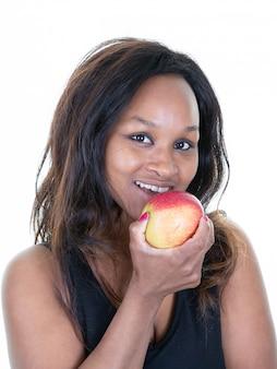 Ritratto della donna di colore graziosa che mangia prendendo morso della mela rossa Foto Premium