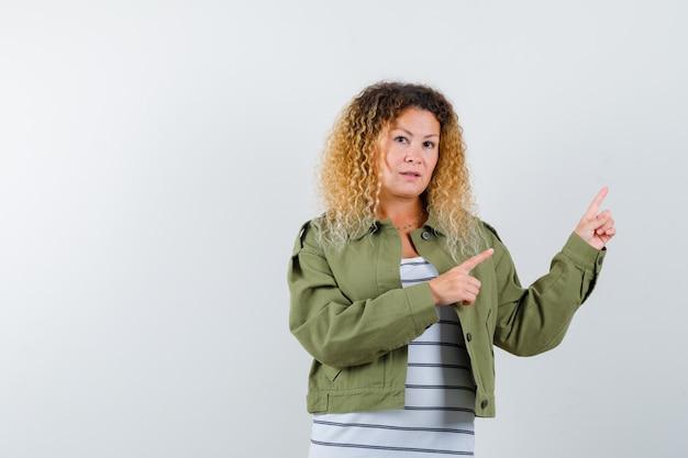 Ritratto di donna abbastanza bionda che punta all'angolo in alto a destra in giacca verde e guardando la vista frontale esitante