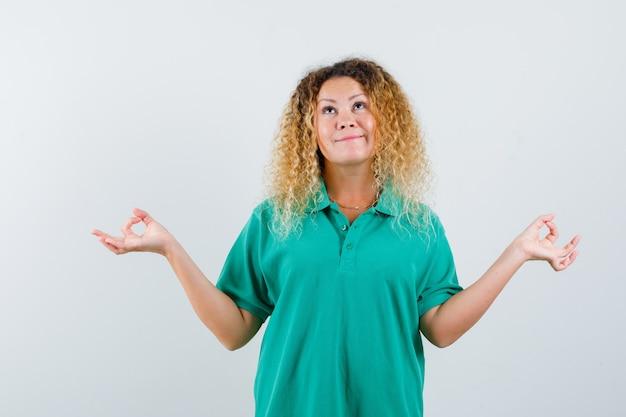 Ritratto di donna abbastanza bionda che mostra gesto di yoga in maglietta polo verde e guardando vista frontale ottimista