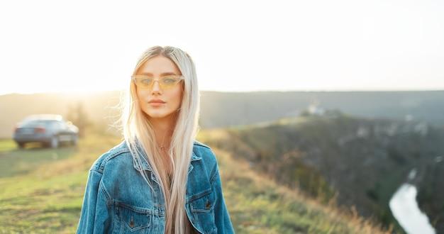 Ritratto di bella ragazza bionda in giacca di jeans che indossa occhiali da sole gialli sullo sfondo del tramonto.