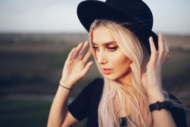 Ritratto di bella ragazza bionda che indossa cappello nero all'aperto.